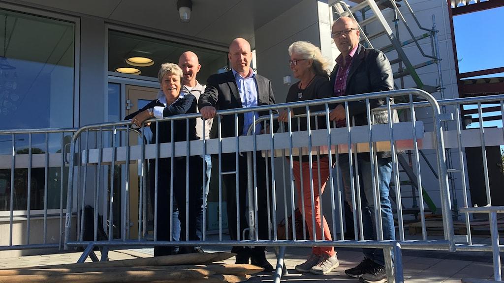 Två kvinnor och tre män som står bakom ett metallstaket.