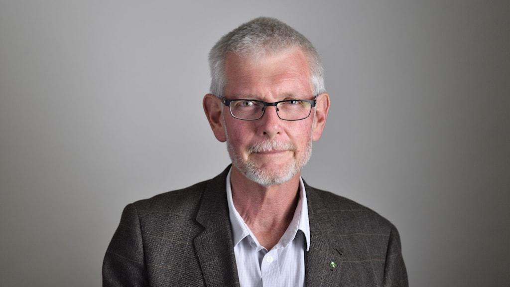 Porträttbild av gråhårig man med glasögon.