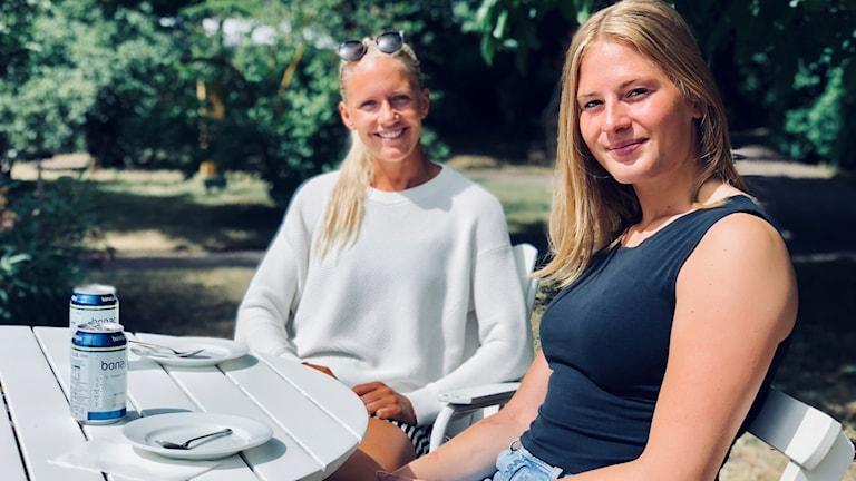 Två tjejer som fikar i solen