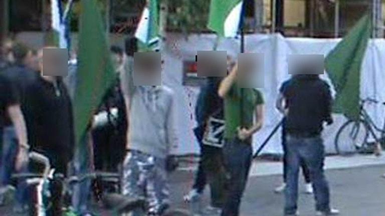 Bild ur polisens förundersökning visar män med flaggor.