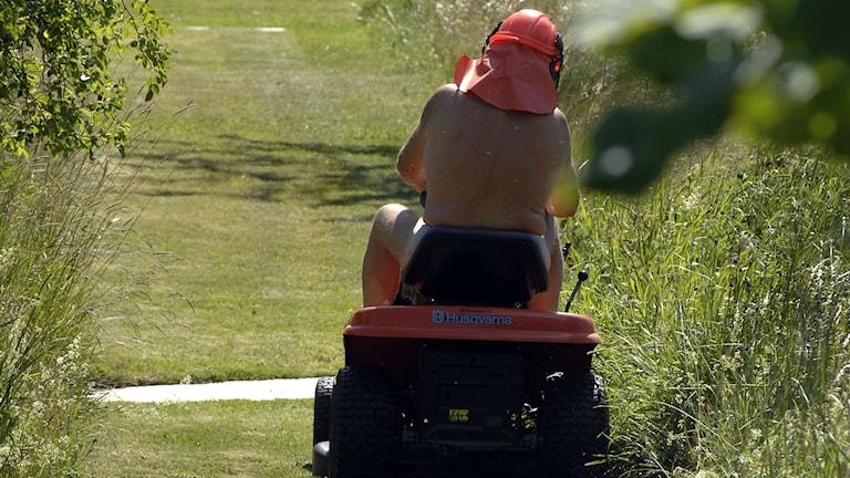 Man klipper gräs med åkergräsklippare.