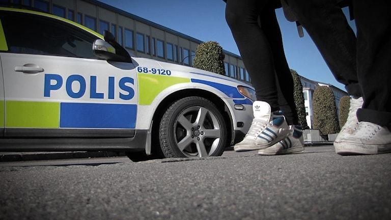 Två ungdomar som passerar en polisbil.