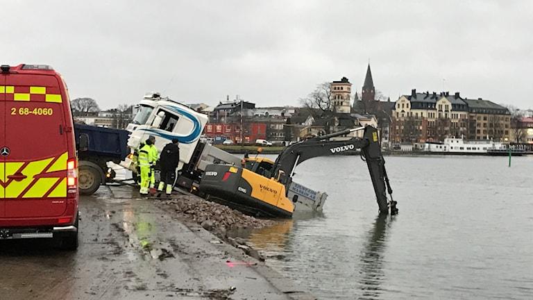 En lastbil och en grävmaskin som hamnat i vattnet vid Slottsholmen i Västervik