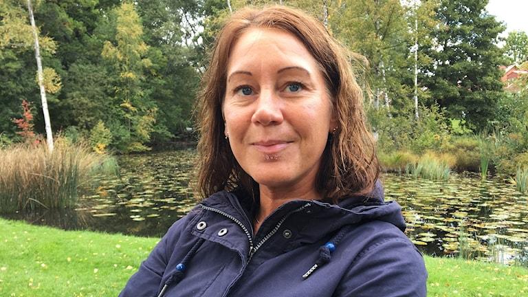 Porträtt på Ann-Sofie Engman med träd i bakgrunden.