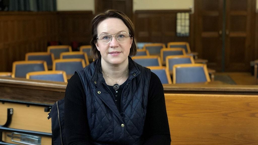 En kvinna sitter på en bänk. Blå stolar syns i bakgrunden.