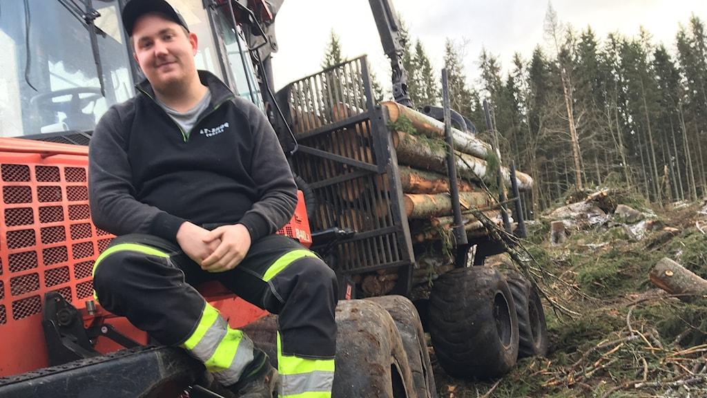 Rasmus Larsson sitter på framdäcket på en stor skogsmaskin.