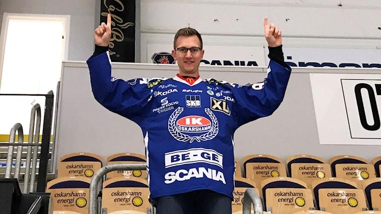 Tom Linder står på en läktare i en ishall med IK Oskarshamns matchtröja på.