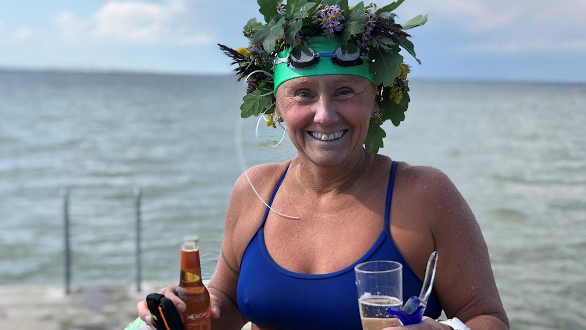 En kvinna i baddräkt och badmössa, med krans på huvudet. Håller flaska och glas i handen. I bakgrunden hav.