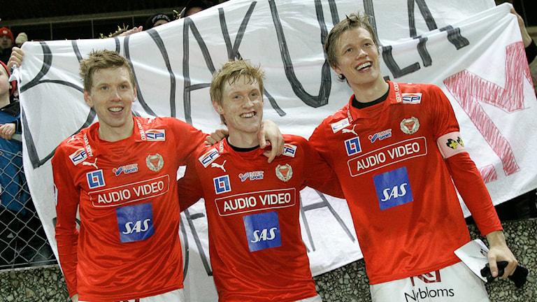 David, Rasmus och Viktor Elm framför Broakullaflagga.