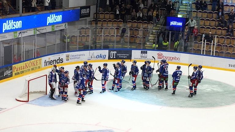 Ett ishockeylag som tackar sin målvakt efter matchen.