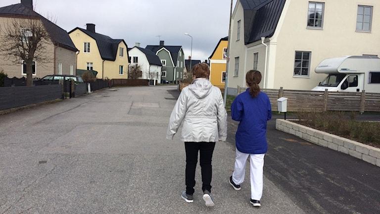 Två kvinnor, en patient och en sjukgymnast tar promenad genom ett kvarter i Västervik.