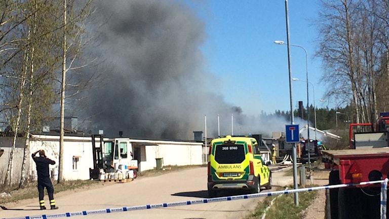 Kraftig rök från en byggnad, räddningspersonal och ambulans syns i bild.