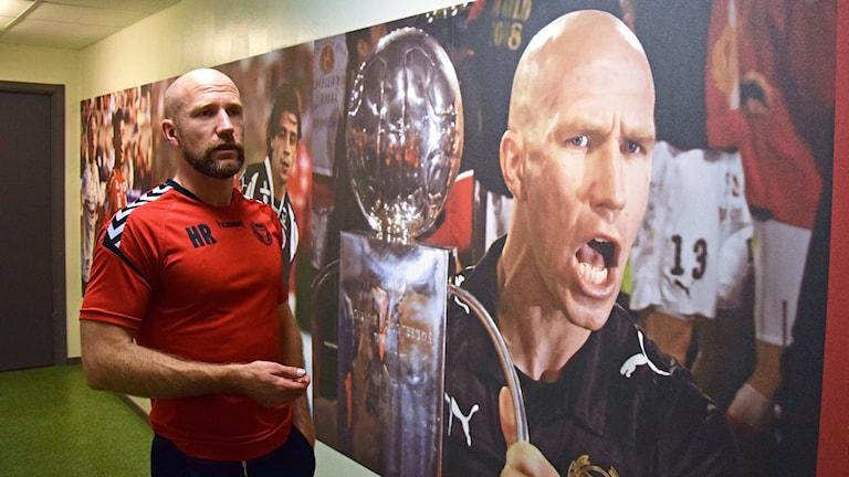 Henrik Rydström står bredvid en vägg med ett stort foto på just Henrik Rydström som håller i en pokal.