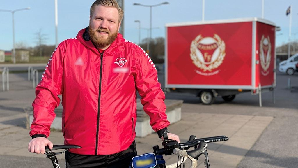 Måns Linge i rågblont skägg och hår stör i röd jacka bakom en cykel.