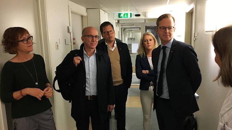 Mikael Damberg omgiven av människor i en korridor.