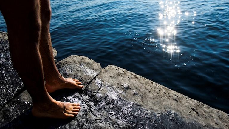 Person barfota på klippkant vid vatten.