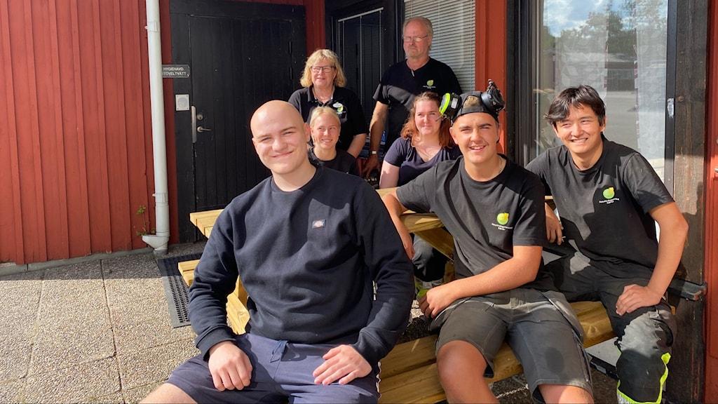 En bild på 7 personer runt en bänk utomhus.