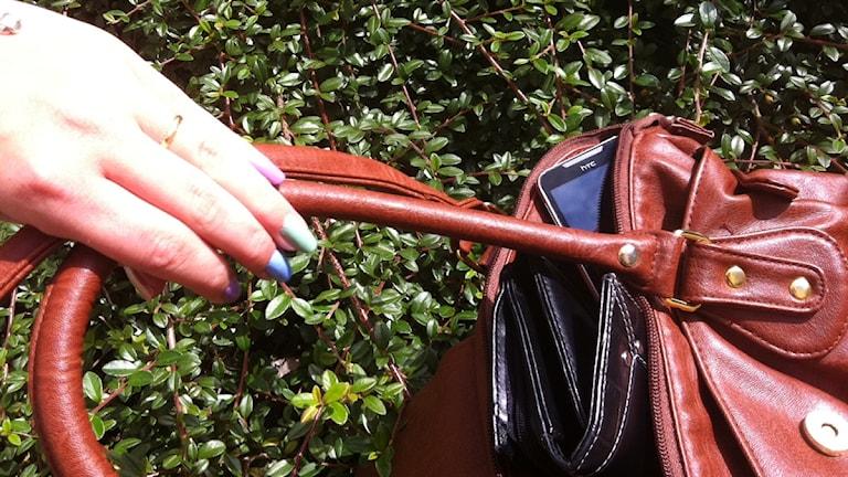 Handväska med mobiltelefon och plånbok.
