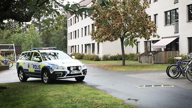 Polisbil utanför flerfamiljshus.