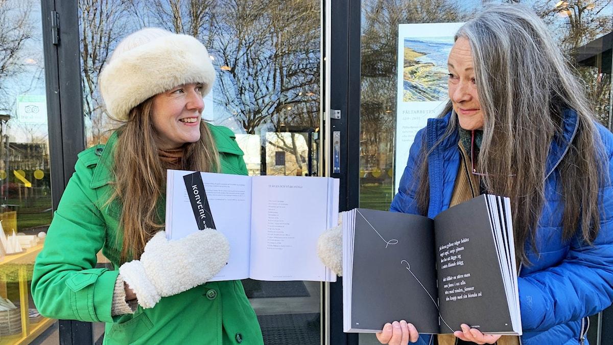 Två personer står bredvid varandra och håller i varsin bok.