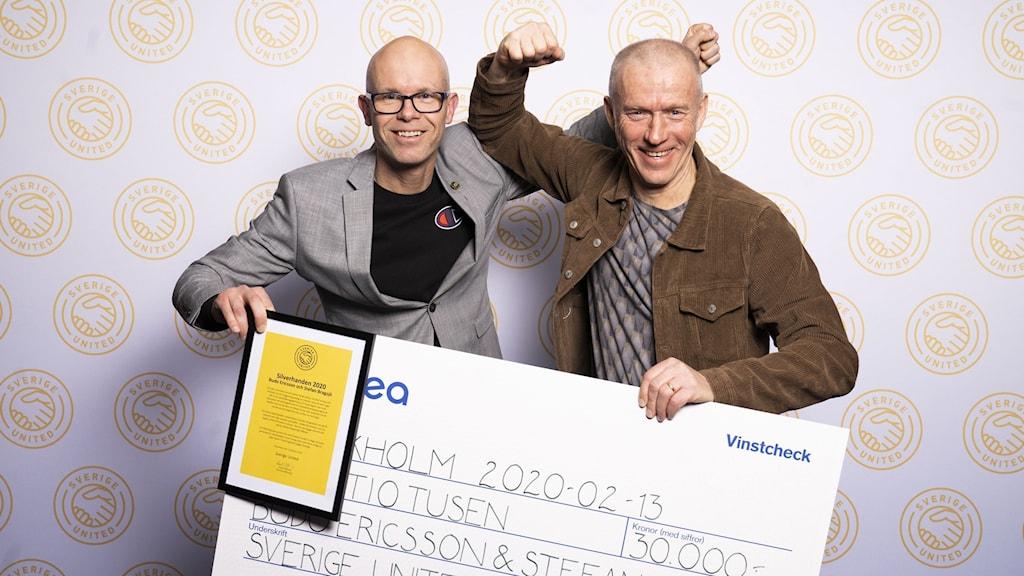 En män som håller i en stor check.