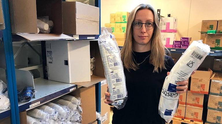En kvinna som håller i rör med vita plastmuggar.