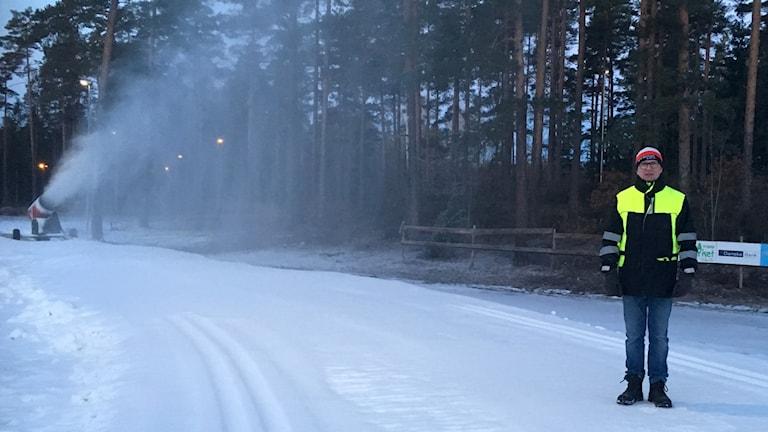 En vinterklädd man står i ett skidspår. En snökanon sprutar snö i bakgrunden.