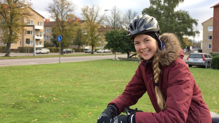 Frida Svensson på cykel med väg och gräsmatta i bakgrunden