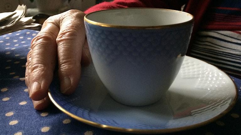 En äldre tant håller i en kaffekopp.