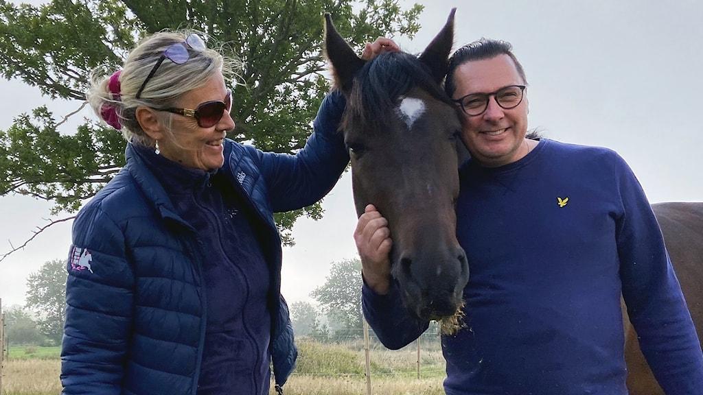 Två personer står på varsin sida om en häst.