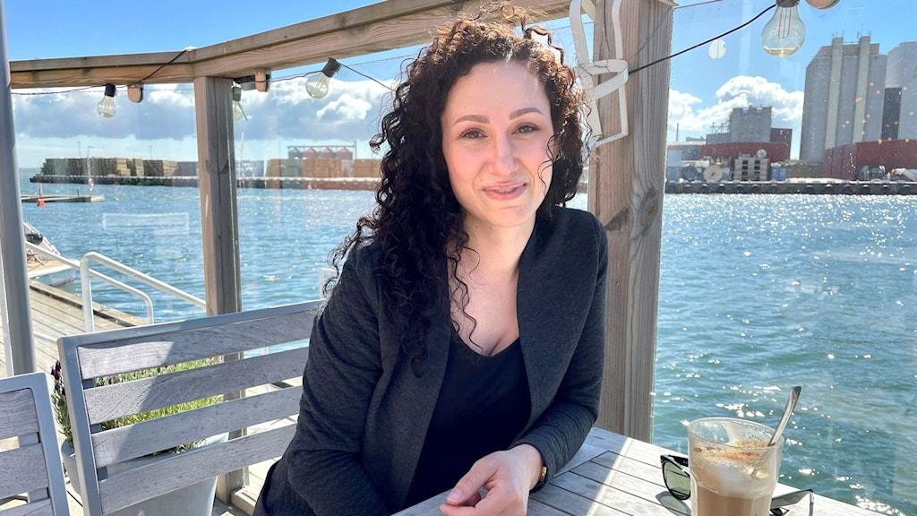 Kvinna sitter vid ett bord utomhus med vatten i bakgrunden.
