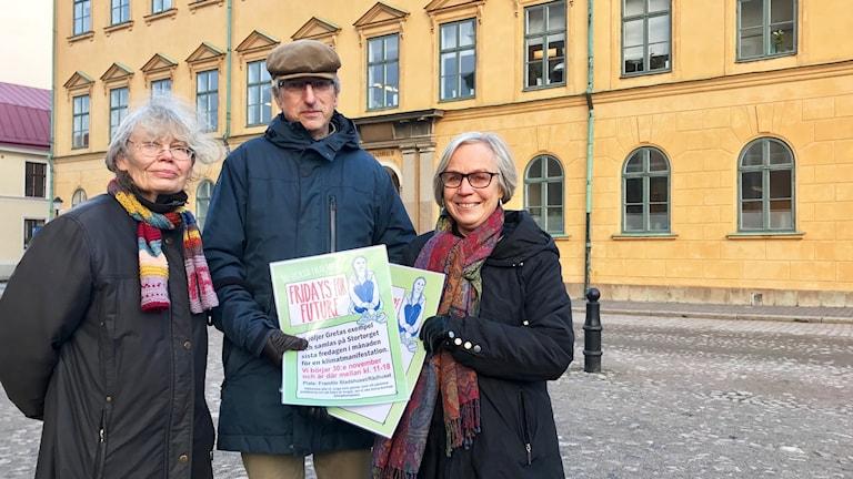 Ann Hammar, Thomas Lundberg och Aina Hagberg står på ett torg i Kalmar och håller i affischer.