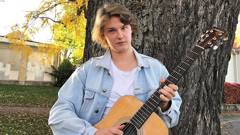 Axel Lindeberg håller i en gitarr framför ett träd.
