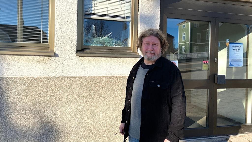 Daniel Söderqvist står framför ett krossat fönster