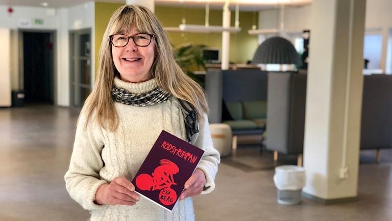 Kvinna poserar i kontorsmiljö och håller i en bok.