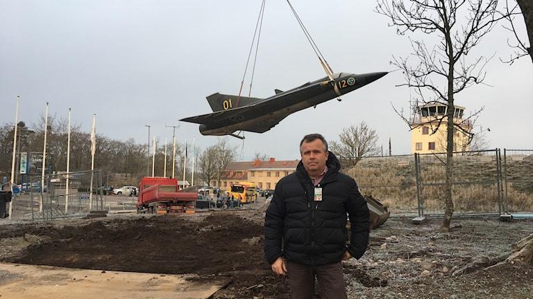 Ronny Lindgren framför Drakenplanet som hänger i vajrar i luften.