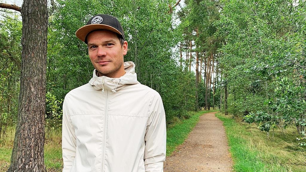 Löparen Joel Eliasson står på en skogsväg med händerna i byxfickorna. Keps och vit jacka är han klädd i.