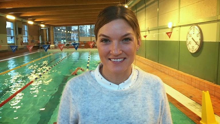 Åsa Lundström framför en simbassäng.