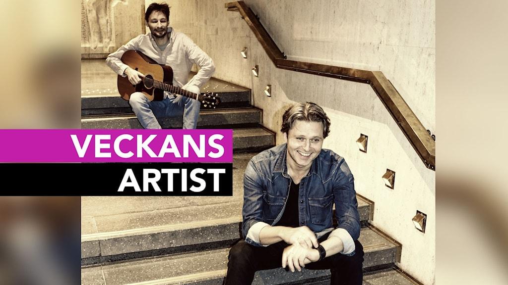 Två killar sitter i en trappa, den ena med en gitarr.