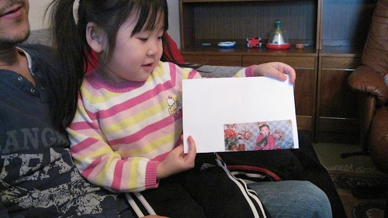 Lois Park med den enda bilden familjen har på Lois storasyster som är kvar inne i Nordkorea. Nu utvisas familjen från Sverige. Foto: Sveriges Radio