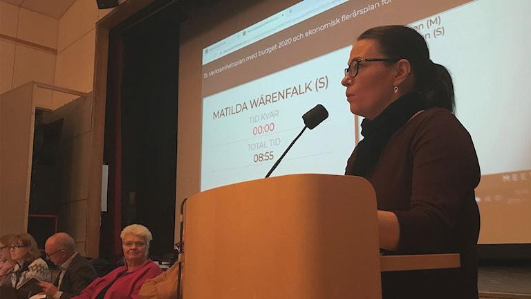 Kvinna står i talarstol i kommunfullmäktige