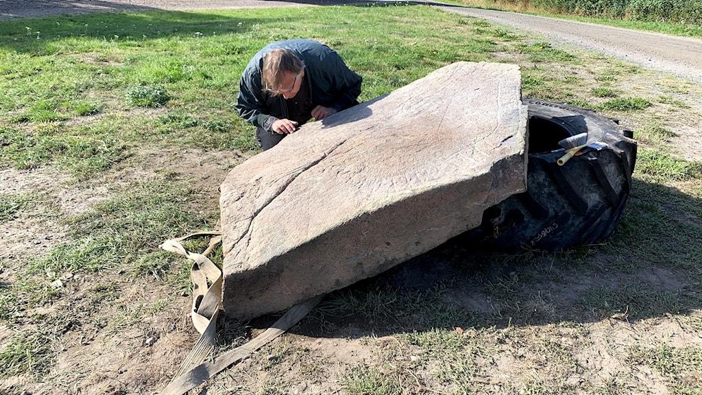 En man som undersöker en nyupptäckt runsten.