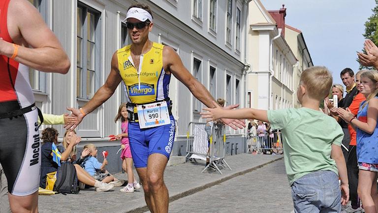 Löpare gör handklapp med publiken på Ironman