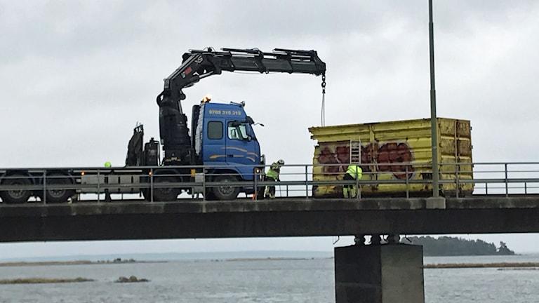 Personal flyttar en container på Ölandsbron.