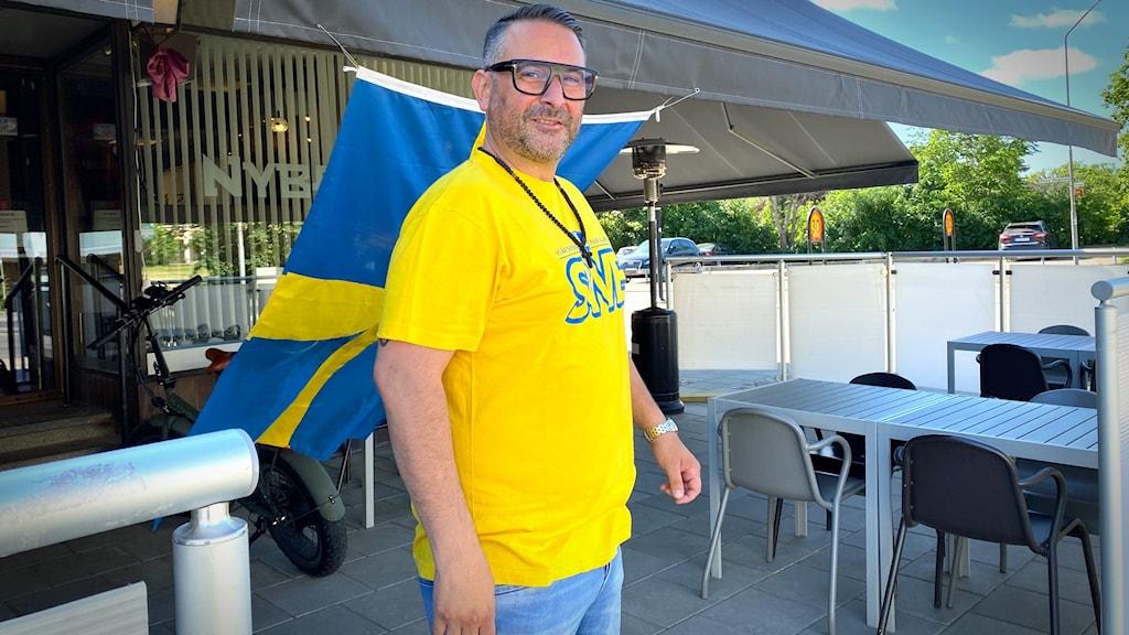 Man står i Sverigekläder på en uteservering.