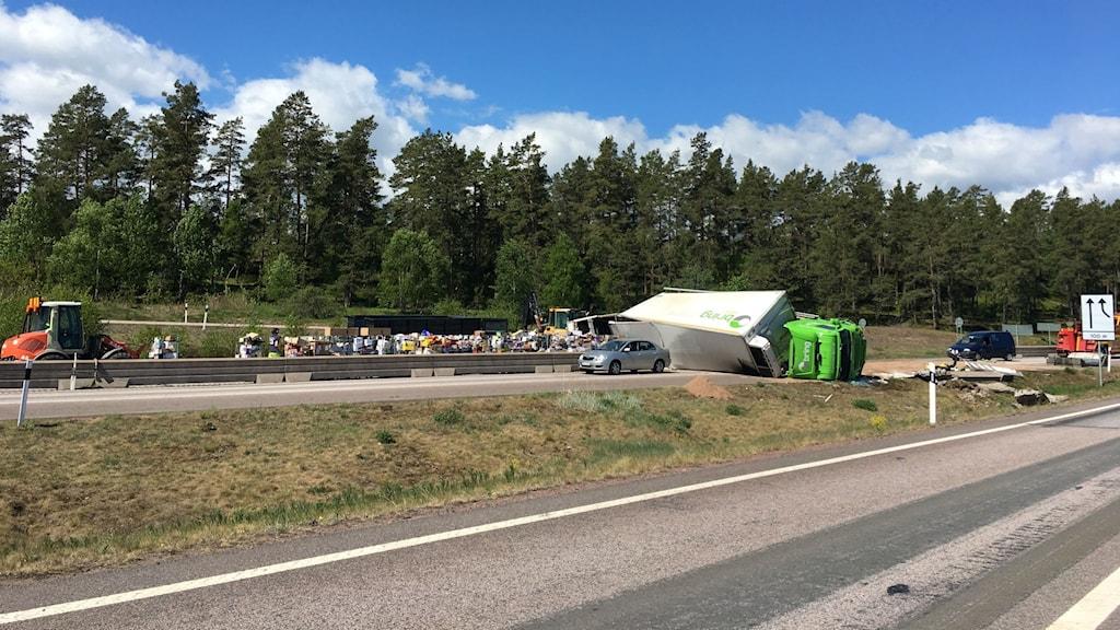 Lastbil med släp ligger på sidan på E22.