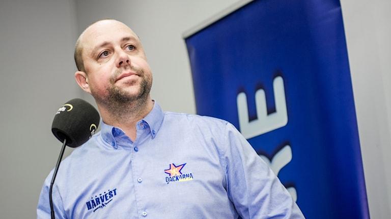 Dackarnas lagledare Mikael Karlsson står vid en mikrofon på en pressträff