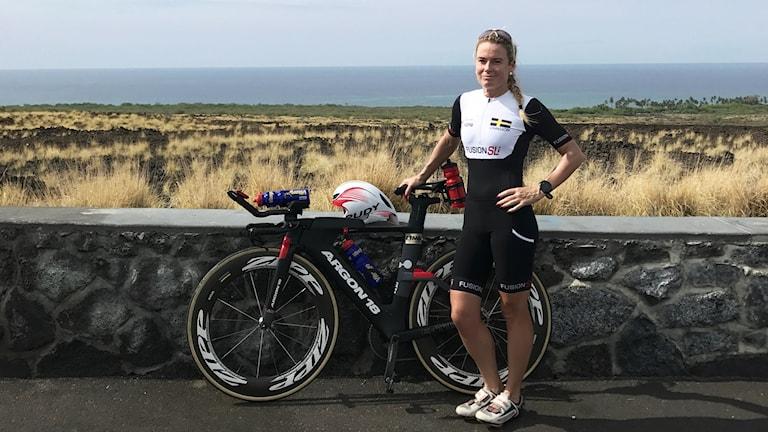 Viktoria Johnsson står med en cykel.