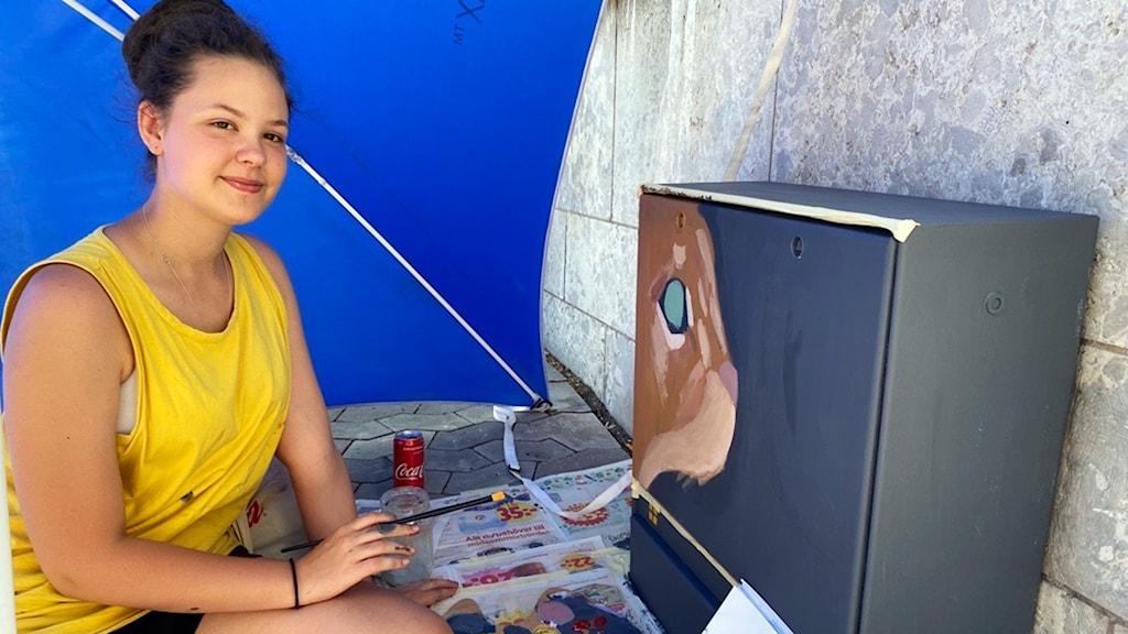 Gatukonstnär målar ett elskåp.