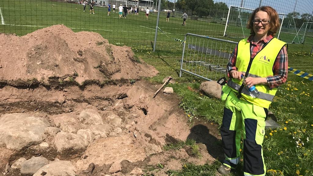 arkeolog framför en av utgrävningsgroparna